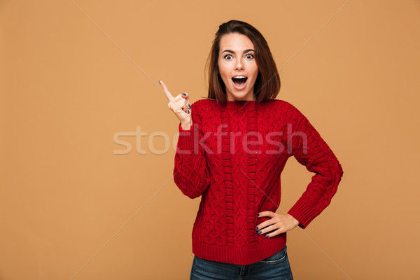 Happy young woman with opened mouth pointing with finger up, loo Stock photo © deandrobot