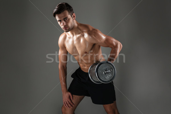 Young concentrated sports man make sports exercises Stock photo © deandrobot
