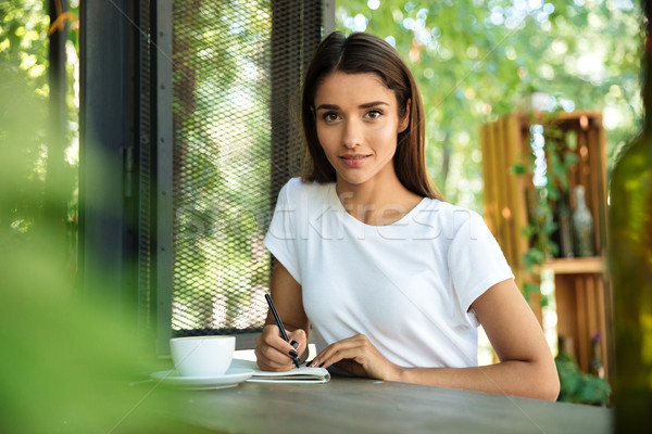 Portrait of a young beautiful girl making notes in a textbook Stock photo © deandrobot