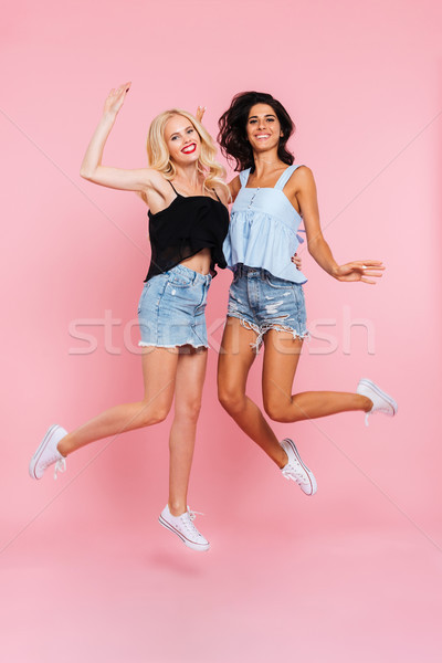 Full length image of two cheerful women in summer clothes Stock photo © deandrobot