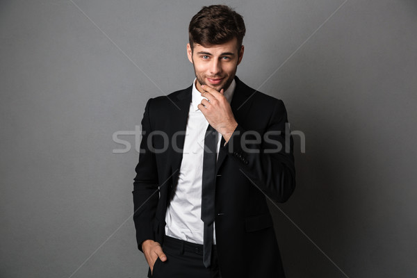 Confident guy in black suit holding his chin, looking at camera Stock photo © deandrobot