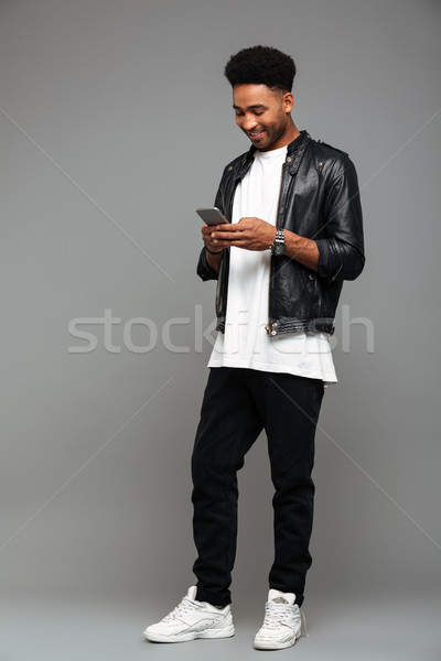 Full length photo of happy attractive afro american man typing m Stock photo © deandrobot