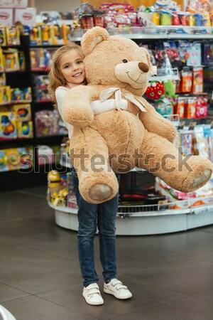 Sorridente little girl grande ursinho de pelúcia em pé Foto stock © deandrobot