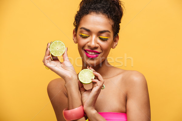 Portrait of pleased afro american woman with trendy makeup holdi Stock photo © deandrobot