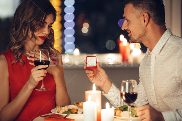 Pretty woman shocked about her man giving her an engagement ring in red box Stock photo © deandrobot