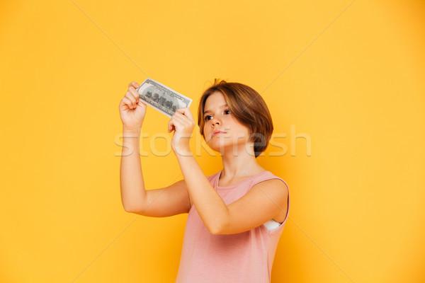 Ernstig meisje naar bankbiljet geïsoleerd dollar Stockfoto © deandrobot