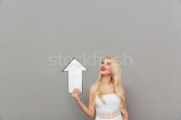 Portrait of a happy woman pointing away with an arrow and looking at camera isolated over gray backg Stock photo © deandrobot