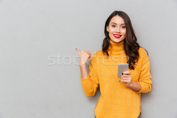 Smiling brunette woman in sweater with smartphone pointing at copyspace Stock photo © deandrobot