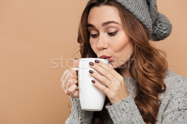 Close-up photo of pretty brunette woman in warm clothes drinking Stock photo © deandrobot