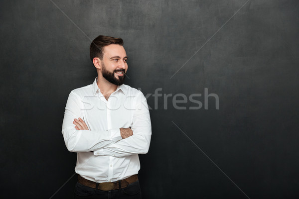 Portrait of positive man in white shirt standing with arms folde Stock photo © deandrobot