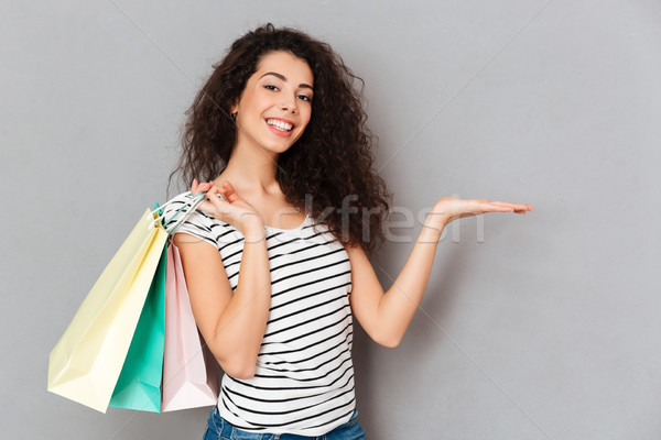 Cheerful female shopaholic being excited with all purchases and  Stock photo © deandrobot