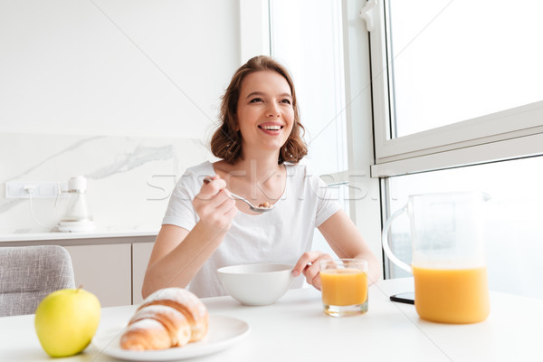 Portrait of happy woman in white tshirt eating healthy porridge  Stock photo © deandrobot