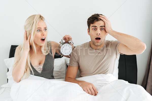 Shocked young couple sitting in bed with opened mouth and holding alarm clock Stock photo © deandrobot