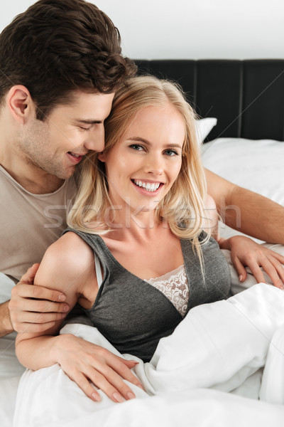 Portrait of beautiful couple smiling andlooking camera while lying in bed Stock photo © deandrobot