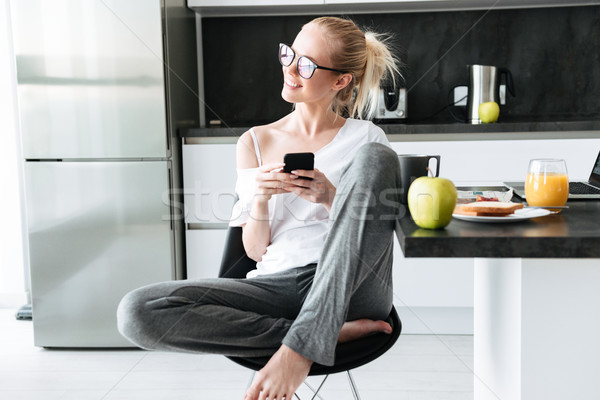 Young attractive lady looking aside while using smartphone Stock photo © deandrobot