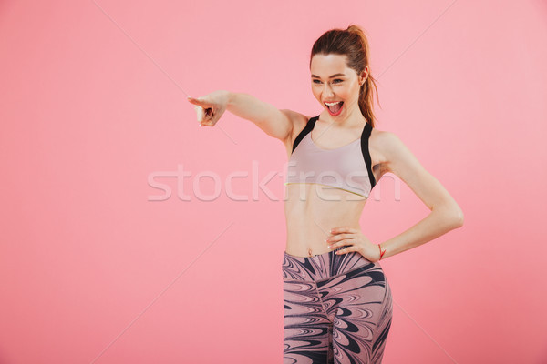 Pleased sportswoman with arm on hip pointing and looking away Stock photo © deandrobot