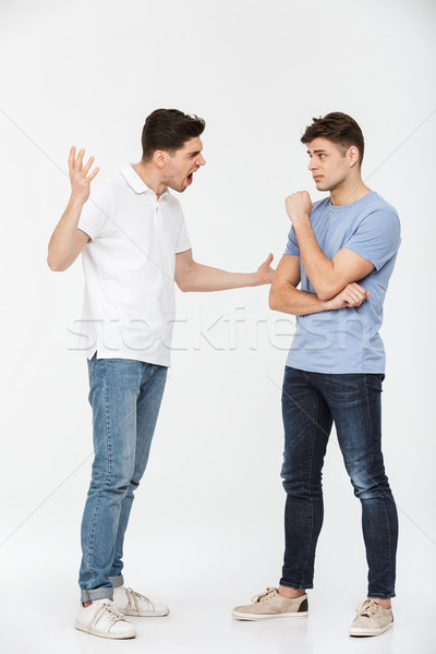 Full length portrait of two angry young men arguing Stock photo © deandrobot