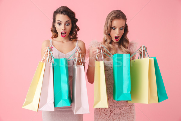 Two shocked women in dresses opening their packages with purchases Stock photo © deandrobot