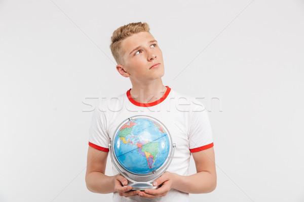 Portré töprengő tizenéves fiú tart földgömb izolált Stock fotó © deandrobot