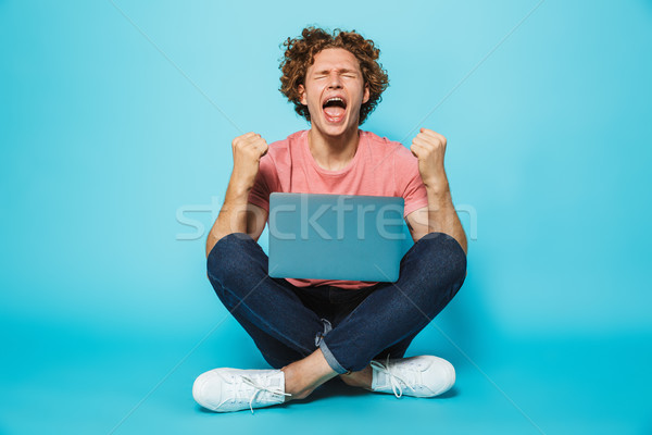 Image of pleased joyous man 20s with brown curly hair rejoicing  Stock photo © deandrobot