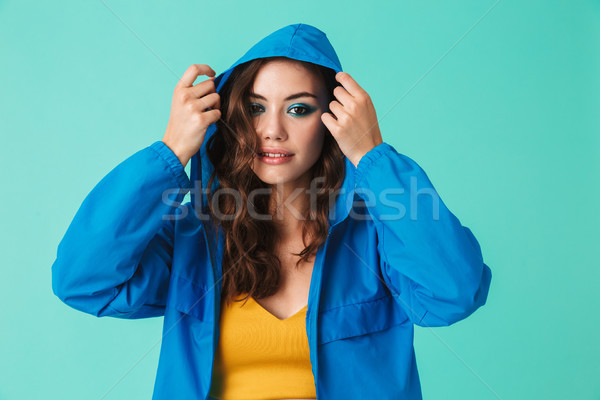 Photo of european young woman 20s in streetwear putting on hood  Stock photo © deandrobot