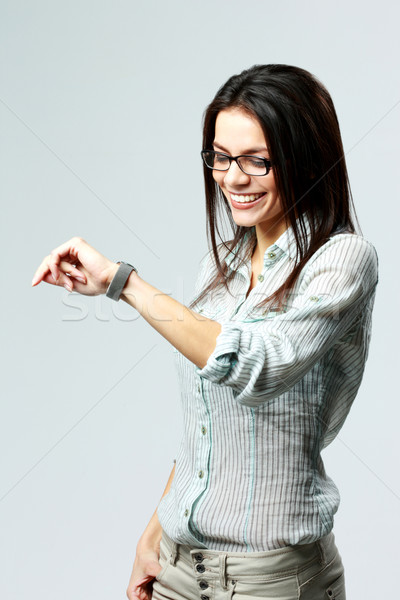 Young happy businesswoman looking at her watch on wrist on gray background Stock photo © deandrobot