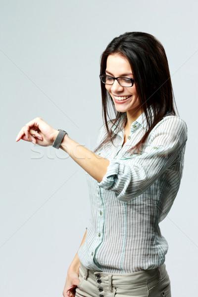 Fiatal boldog üzletasszony néz óra csukló Stock fotó © deandrobot