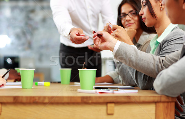 Businessman handing out a business card in meeting Stock photo © deandrobot