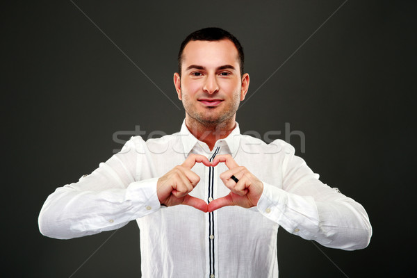 happy man making heart from his hands on black background Stock photo © deandrobot