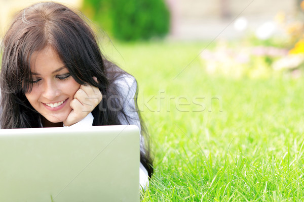 Young beautiful smiling woman using laptop on campus/home yard. Sunny day. Stock photo © deandrobot