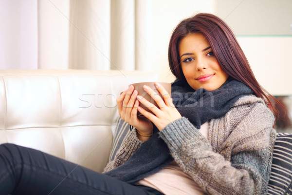 Happy young woman sitting on sofa in cosy cloths with cup of coffee Stock photo © deandrobot