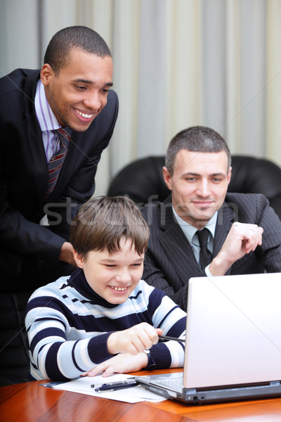 Kid boy explains multi ethnic business team how to work Stock photo © deandrobot