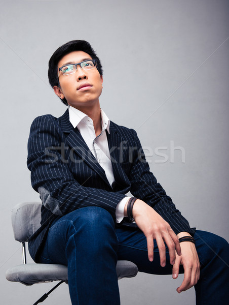 Pensive young businessman sitting on the chair Stock photo © deandrobot