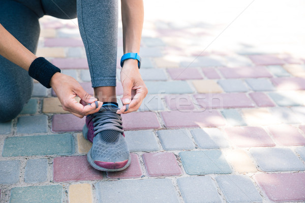 Female hands tying shoelaces Stock photo © deandrobot