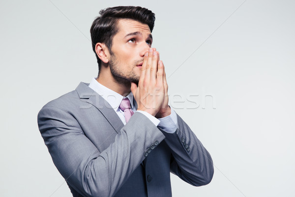 Businessman praying over gray background Stock photo © deandrobot