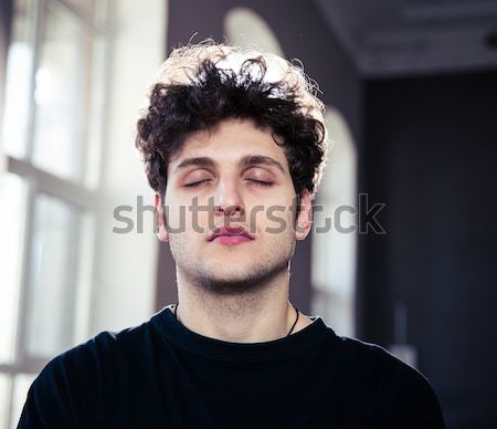 Portrait of a handsome young man looking at camera Stock photo © deandrobot