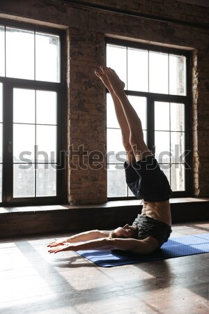 Happy young woman doing exercise on yoga mat Stock photo © deandrobot