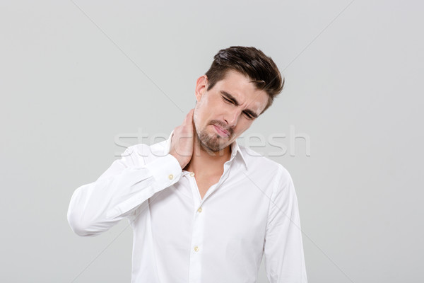 Attractive man have a neck pain Stock photo © deandrobot