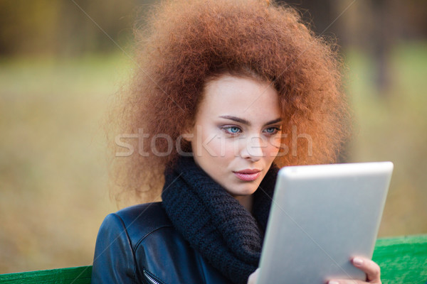 Woman with curly hair using tablet computer outdoors Stock photo © deandrobot