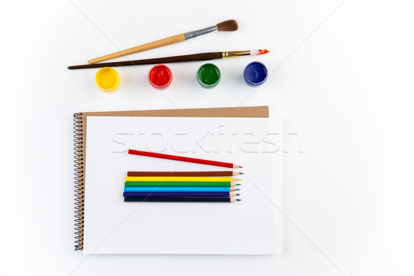 Top view of sketchbook, paintbrushes, colorful pensils and gouache paints  Stock photo © deandrobot