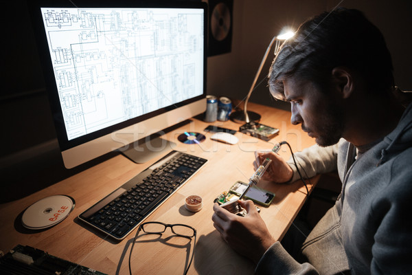 Serious man using soldering iron for fixing smartphone  Stock photo © deandrobot