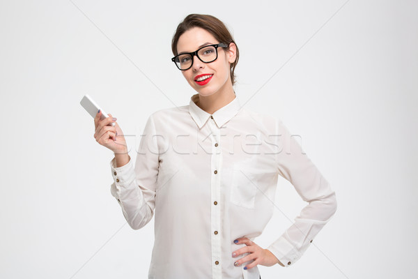 Smiling confident young business woman standing and holding smartphone  Stock photo © deandrobot