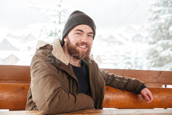 Cheerful man sitting outdoors in winter Stock photo © deandrobot