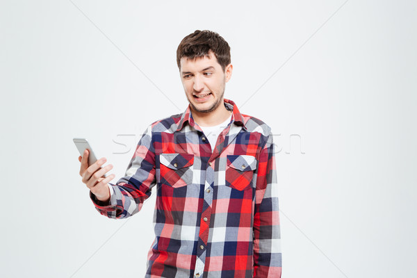 Man with disgust emotion holding smartphone Stock photo © deandrobot