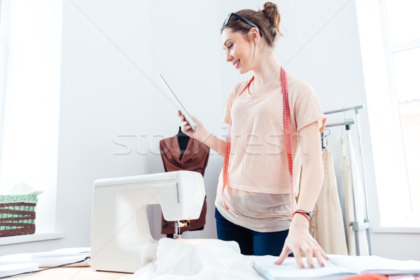 Happy woman seamstress with laptop working in design studio  Stock photo © deandrobot