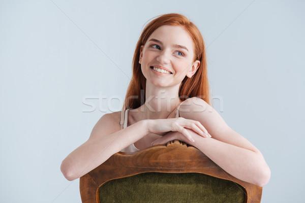 Mosolyog vörös hajú nő nő ül szék másfelé néz Stock fotó © deandrobot