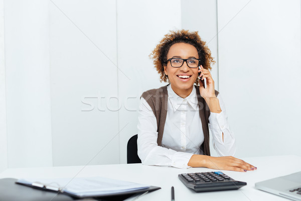 Happy african woman accountant sitting and talking on cell phone Stock photo © deandrobot