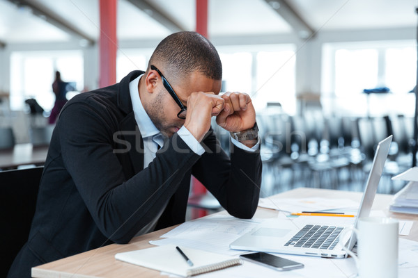 Exhausted businessman at his desk Stock photo © deandrobot