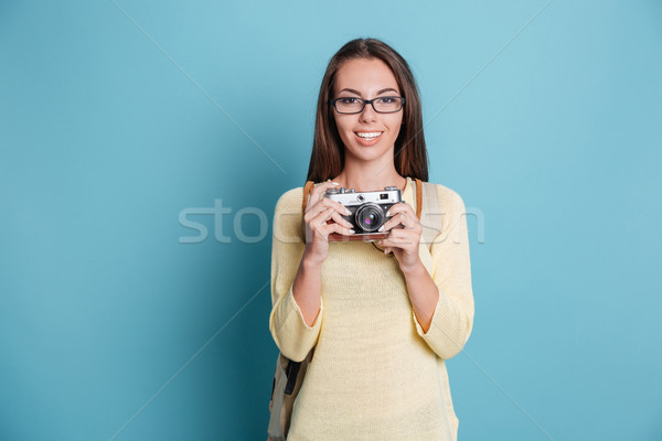 Young pretty girl taking photo using photocamera over blue background Stock photo © deandrobot