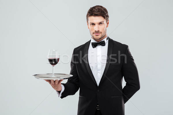 Waiter in tuxedo holding glass of red wine on tray Stock photo © deandrobot